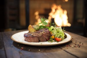 Delicious grilled stake and potatoes served on a wooden table, fireplace on background