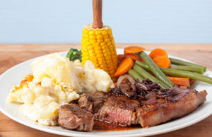 A sliced juicy rump steak cooked to medium, with mashed potatoes and vegetables